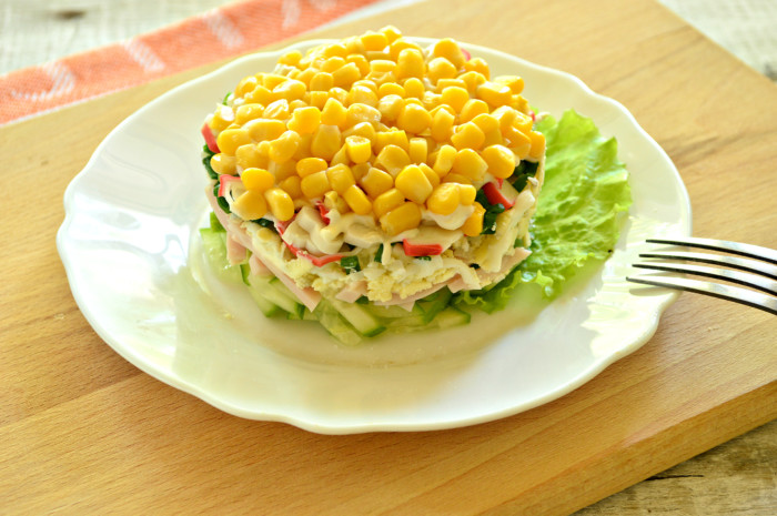 Дуже смачний листковий салат з крабовими паличками, кукурудзою та шинкою в кільці
