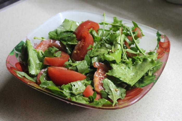 Салат з руколою і помідорами, листям салату та щавлем, заправлений гарбузовим маслом